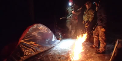 Fire Burning in front of a Survival Shelter